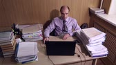 executive : Office worker sits at a table in office, he works on a laptop, large piles of documents on the table