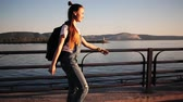 blading : Young stylish funky girl riding roller skates a near sea with a backpack Stock Footage