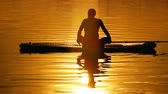 chakra : A young man floats slowly on the paddle board