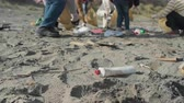 spolupracovat : Group of volunteers picking up trash on the beach. Selective focus on plastic bottle in foreground