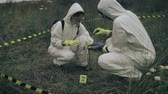 радиоактивный : Two people with bacteriological protection equipment picking up evidence into a plastic bag next to corpse outdoors