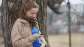 doğurganlık : Young pregnant serious girl in beige vintage rare coat and royal blue tshirt tapping her smartphone on countryside landscape in front of big tree, Steady cam, slow mo shot