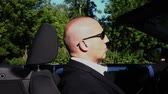 sideview : a business man is driving a convertible car in a landscape, perspective side view Stock Footage