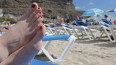 banho de sol : Female feet on a deckchair on the beach