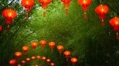 шуй : Rows of traditional chinese style red lanterns hanging on bamboo tree tunnel arch.