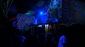 namalovaný : PHANGAN, THAILAND - MARCH 16, 2018: Shiva Moon Goa Trance Party. Psychedelic neon and luminescent decoration of dance floor and dj stage. Young people have fun on the tropical event.