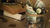accountancy : Books with glass penny jar filled with coins and banknotes. Tuition or education financing concept. Scholarship money. Savings for future education. Books, glasses, clock in background. Soft focus