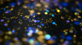 paillet : Defocused shimmering multicolored glitter confetti, black background. Party, magic, imagination. Rainbow colors, sparkle circles. Holiday abstract festive texture of shiny blurred bokeh light spots. Stockvideo