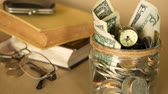 penny : Books with glass penny jar filled with coins and banknotes. Tuition or education financing concept. Scholarship money. Savings for future education. Books, glasses, clock in background. Soft focus