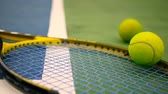 oyun alanı : Close up of tennis equipment on the court. Sport, recreation concept. Yellow racket with a tennis ball in motion on a clay green blue court next to the white line with copy space and soft focus. Stok Video