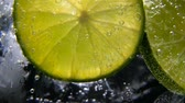 охлажденный : Macro close-up,refreshing soda tonic fizzy water, lime in Glass, ice. Slice of lemon, mineral bubbles. Detox or thirst concept. Healthy, dietary nutrition. Cold lemonade mojito drink. Black background