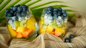 ananas : Colorful tropical mix salad in jar. Fresh various kind of raw organic berry and fruit in glass bowl. Healthy vegetarian eating, balanced, vegan diet. Rustic food background with falling blueberrys