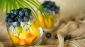 mirtilo : Colorful tropical mix salad in jar. Fresh various kind of raw organic berry and fruit in glass bowl. Healthy vegetarian eating, balanced, vegan diet. Rustic food background with falling blueberrys