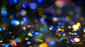 lentejuela : Defocused shimmering multicolored glitter confetti, black background. Party, magic, imagination. Rainbow colors, sparkle circles. Holiday abstract festive texture of shiny blurred bokeh light spots. Archivo de Video