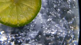 цитрон : Macro close-up,refreshing soda tonic fizzy water, lime in Glass, ice. Slice of lemon, mineral bubbles. Detox or thirst concept. Healthy, dietary nutrition. Cold lemonade mojito drink. Black background