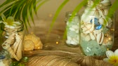 плюмерия : Glass jar of tropical shells for home decor. Marine style, beach themed interior decorating. Bottle filled with seashells, corals, marine items with bokeh lights and plumeria flowers Стоковые видеозаписи