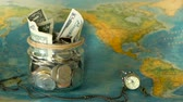 tirelire : Travel budget concept. Money saved for vacation in glass jar on world map background, copy space. Banknotes and coins for adventure. Savings for journey. Collecting money for trip. Moneybox with cash.