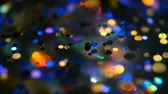 cicili bicili : Defocused shimmering multicolored glitter confetti, black background. Party, magic, imagination. Rainbow colors, sparkle circles. Holiday abstract festive texture of shiny blurred bokeh light spots. Stok Video
