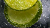 tonic : Macro close-up,refreshing soda tonic fizzy water, lime in Glass, ice. Slice of lemon, mineral bubbles. Detox or thirst concept. Healthy, dietary nutrition. Cold lemonade mojito drink. Black background