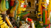 важный : Wooden miniature guardian spirit house. Small buddhist temple shrine, colorful flower garlands. San phra phum erected to bring fortune. Traditional respect animistic rituals, pray ceremonies Стоковые видеозаписи