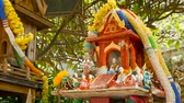 crença : Wooden miniature guardian spirit house. Small buddhist temple shrine, colorful flower garlands. San phra phum erected to bring fortune. Traditional respect animistic rituals, pray ceremonies Stock Footage