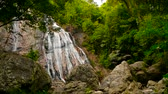 patak : Jungle paradise landscape of tropical country. Waterfall cascade in green rain forest. Motion of water flow from cliff down. Exotic river and rocks. Natural seasonal travel outdoor background