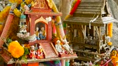 croire : Wooden miniature guardian spirit house. Small buddhist temple shrine, colorful flower garlands. San phra phum erected to bring fortune. Traditional respect animistic rituals, pray ceremonies Vidéos Libres De Droits