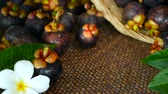 плюмерия : Top view of fresh delicious harvested mangosteens on wooden table. Thai organic purple fruit in the basket. Exotic natural blurred background with tropical flower. Healthy food and eating concept.