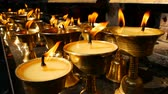 sacred festival : Burning candles in temple. View of golden shiny bowls with burning flame of oil candles for worship