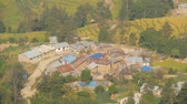 living environment : Small town on foothill from above . View from air of small and poor town placed on green land of Himalayan valley, Nepal. Local houses in Nagarkot