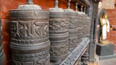 резной : Row of aged religious prayer wheels or drums with mantra Om Mani Padme Hum in yard of temple, Durbar Square, Nepal, Kathmandu. Tibetian buddhism Стоковые видеозаписи