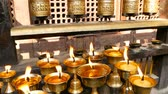 kadidlo : Burning candles in temple. View of golden shiny bowls with burning flame of oil candles for worship