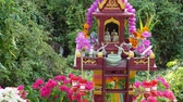 小さな像 : Wooden miniature guardian spirit house. Small buddhist temple shrine, colorful flower garlands. San phra phum erected to bring fortune. Traditional respect animistic rituals, pray ceremonies. 動画素材