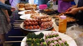 Traditional Asian night street food market in Thailand. Barbecue meatballs and other exotic delicious snacks for sail. Ready to eat food. Stock Footage