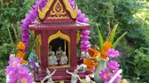 Wooden miniature guardian spirit house. Small buddhist temple shrine, colorful flower garlands. San phra phum erected to bring fortune. Traditional respect animistic rituals, pray ceremonies. 무비클립