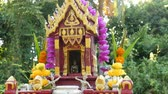 Wooden miniature guardian spirit house. Small buddhist temple shrine, colorful flower garlands. San phra phum erected to bring fortune. Traditional respect animistic rituals, pray ceremonies. Stock Footage