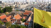roi : Cityscape of modern oriental town. View of houses roofs on streets of majestic Bangkok from Golden Mount Temple during sunset time. Yellow royal flag and symbol of Thailand swaying on the wind.
