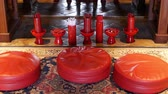 fortune telling : Sticks with predictions in oriental temple. Vases with traditional Seam-Si fortune teller sticks placed on floor in Chinese temple in front of altar. Pillows for knees on the floor on carpet.