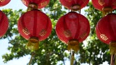китайский квартал : Paper lanterns on shabby building. Red paper lanterns hanging on ceiling of weathered concrete temple building on sunny day between juicy greenery in oriental country. traditional decoration.