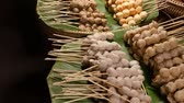köfte : Baskets with BBQ meatballs on street. Stacks of delicious traditional barbecue meatballs on sticks placed on green palm leaves in baskets on street of Thailand