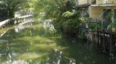 unclean : Oriental slum near channel. Shabby houses of typical oriental slum located near small canal on street of Bangkok on sunny day. Poor traditional living near water in houses on stilts