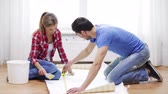 rolo : repair, building and home concept - smiling couple measuring wallpaper