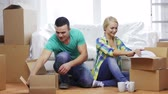 talheres : moving, home and couple concept - smiling couple unpacking boxes with kitchenware in new home Vídeos