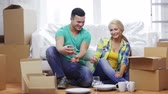 свадьба : moving, home and couple concept - smiling couple unpacking boxes with kitchenware in new home Стоковые видеозаписи