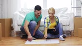 coberto : moving, home and couple concept - smiling couple relaxing on sofa and looking at blueprint in new home Stock Footage