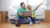 embalagem : moving, home, technology and couple concept - smiling couple with laptop sitting on floor in new house