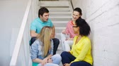 campus : education, communication and happiness concept - group of smiling students sitting on stairs and talking