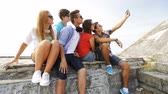 звук : summer vacation, friendship, street life, technology and people concept - group of smiling teenagers hanging out and making selfie outdoors Стоковые видеозаписи