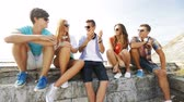 kultura mládeže : summer vacation, friendship, street life, technology and people concept - group of smiling teenagers hanging out and chatting outdoors Dostupné videozáznamy