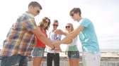 funky : summer vacation, friendship, street life, gesture and people concept - group of smiling teenagers putting hands on top of each other outdoors